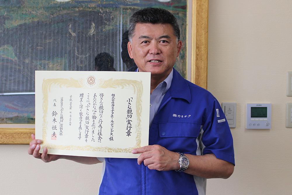 表彰状を持つ上村社長